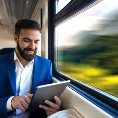 Businessman sitting next to window reading news and surfing internet on his tablet while traveling in comfortable high speed train.